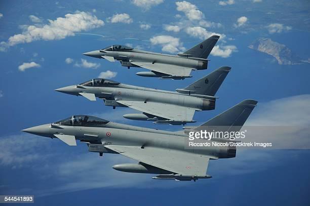 Three Italian Air Force Eurofighter EF2000 Typhoon aircraft in flight over the Mediterranean.