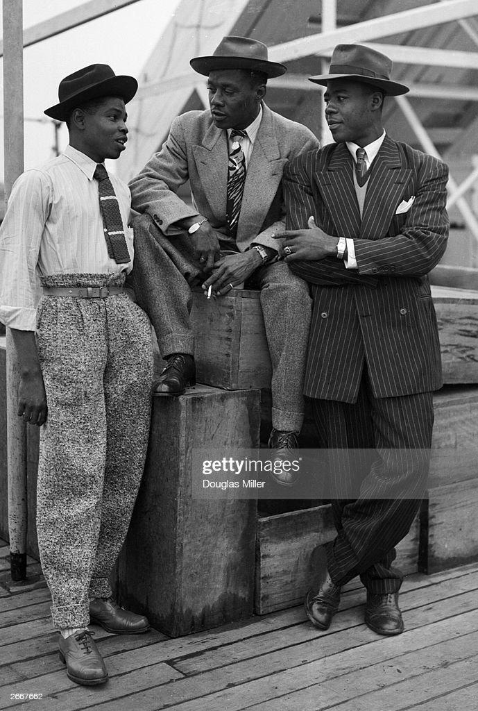 Three Jamaican immigrants (left to right) John Hazel, a 21-year-old boxer, Harold Wilmot, 32, and John Richards, a 22-year-old carpenter, arriving at Tilbury on board the ex-troopship 'Empire Windrush', smartly dressed in zoot suits and trilby hats.