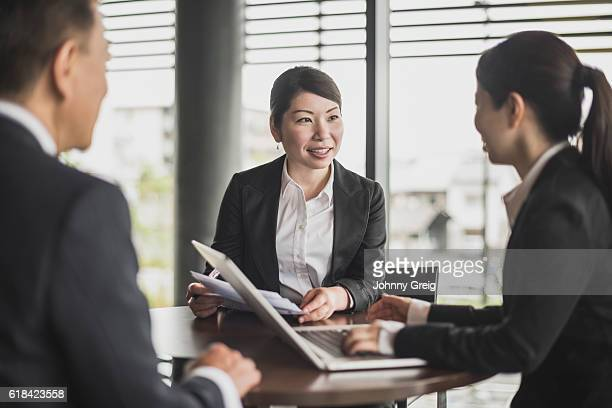 Three Japanese business people meeting in office with laptop