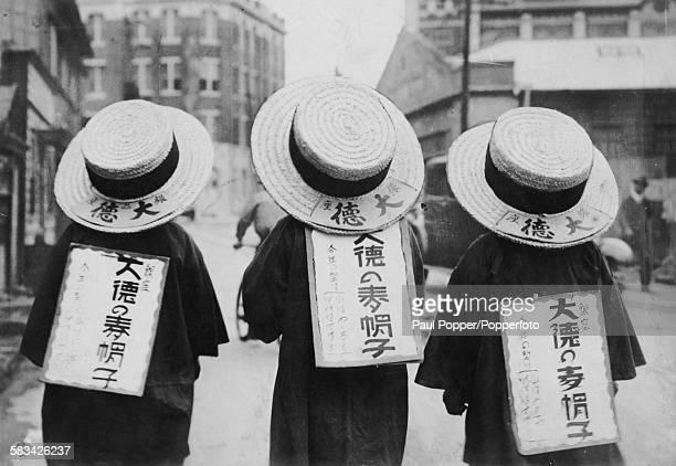 Three Japanese sandwich men or human billboards wearing large straw hats and sandwich boards Tokyo circa 1935