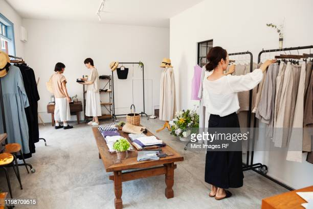 three japanese women standing in a small fashion boutique, looking at clothing on rails. - 衣料品店 ストックフォトと画像