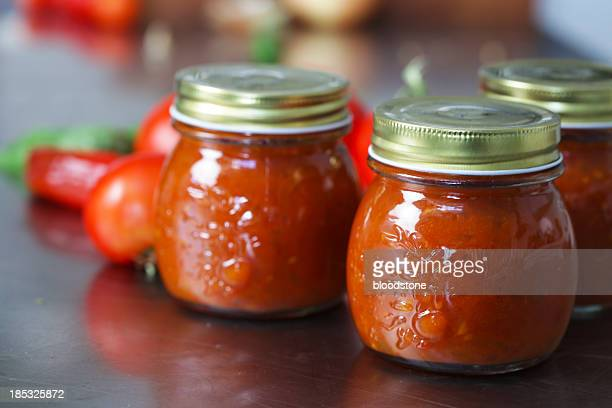 Three jars of tomato chutney on a table with the tomatoes
