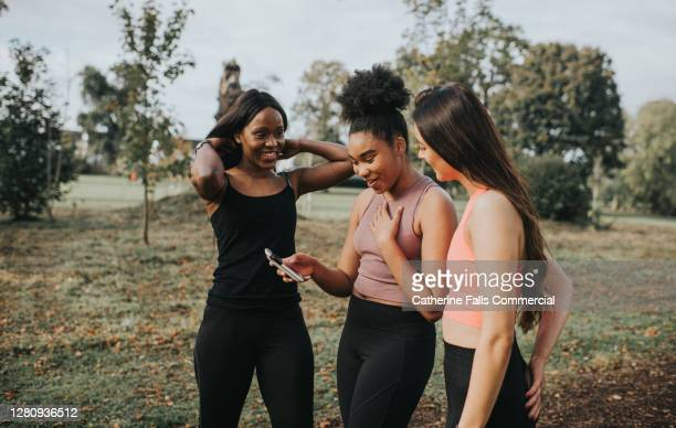 three joggers stop to receive some good news on a mobile phone - portable information device stock pictures, royalty-free photos & images