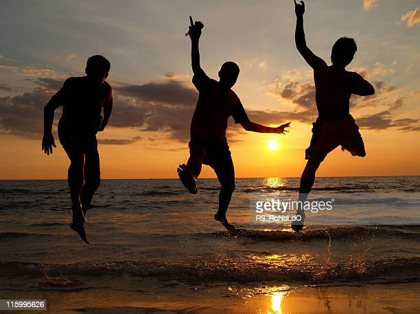 Three jumping men on the beach at sunset in summer
