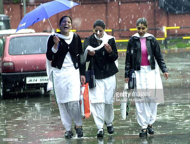 Three Kashmiri Muslim schoolgirls laugh as they are caught in a snow flurry on a street in Srinagar 30 April 2004 The Kashmir valley is experiencing...