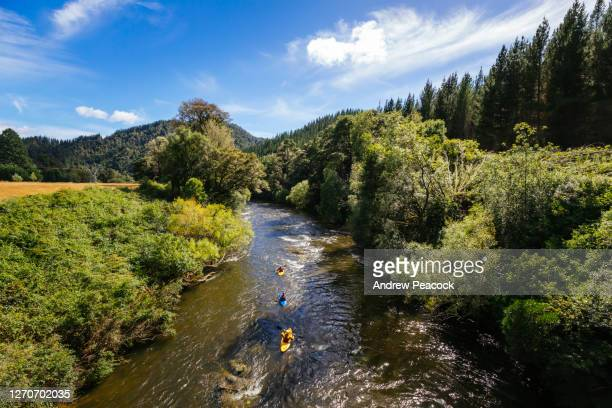 three kayakers crossing mangles river - nelson city new zealand stock pictures, royalty-free photos & images