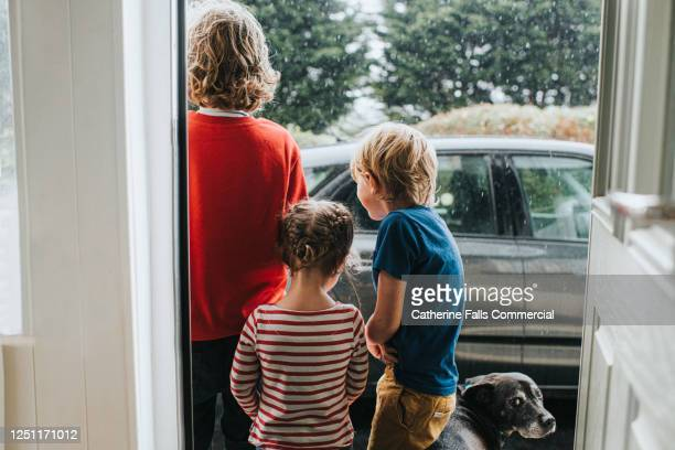 three kids and a dog standing outside front door looking at heavy rain - caucasian appearance stock pictures, royalty-free photos & images
