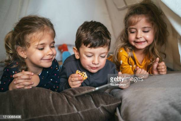 three kids and digital tablet - pillow stock pictures, royalty-free photos & images