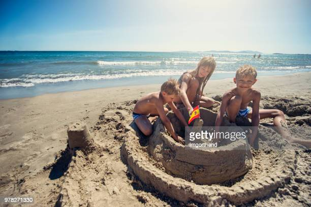 Three kids are building a sandcastle on spanish beach