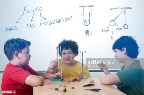 tre ragazzi stanno facendo esperimenti di fisica. - fisica foto e immagini stock