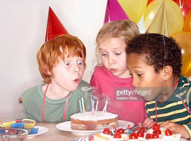 Three kids at a birthday party blowing out candles on cake
