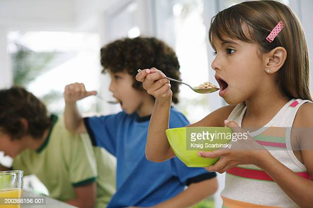Three kids (8-10) at table, eating cereal