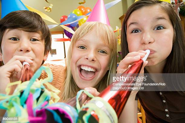 three kids blowing noise makers at birthday party