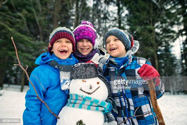 Drei Kinder einen Schneemann bauen, Wintertag