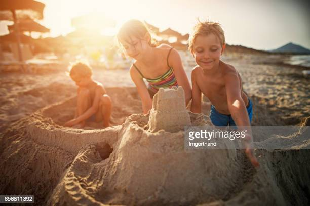 Three kids building sandcastle on beach