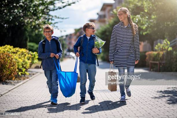 three kids carrying shopping home in resusable shopping bags - reusable bag stock pictures, royalty-free photos & images