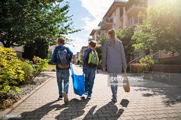 three kids carrying shopping home in resusable shopping bags - city life stock pictures, royalty-free photos & images