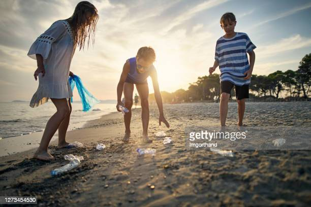 three kids cleaning up the beach - picking up stock pictures, royalty-free photos & images