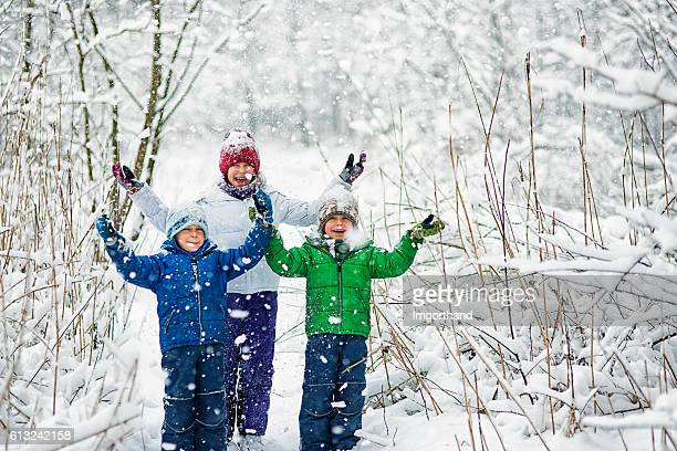 Three kids enjoying first snow.