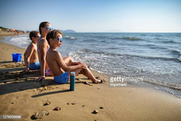 three kids enjoying sitting on the beach - reusable stock pictures, royalty-free photos & images