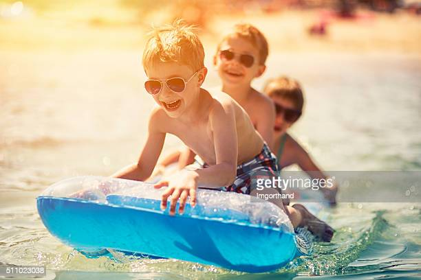 Three kids having fun in sea on air bed