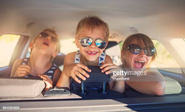 three kids having fun on road trip - family inside car stock photos and pictures