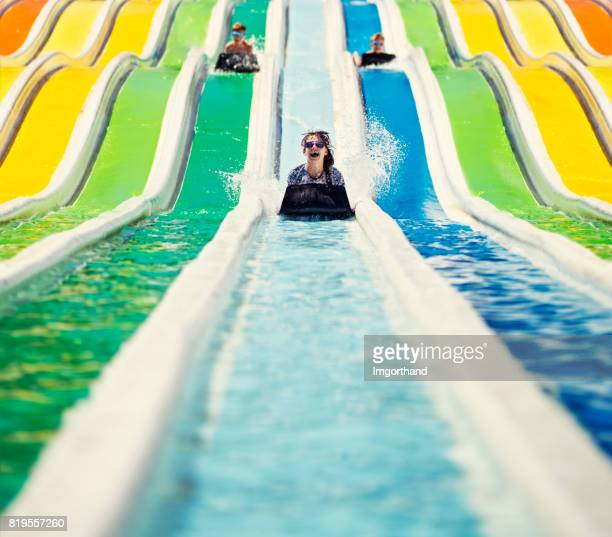 Three kids having fun sliding in a waterpark