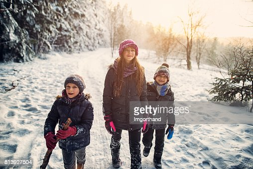 Three kids hiking in beautiful winter forest
