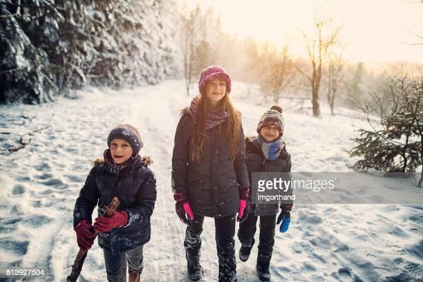Three kids hiking in beautiful winter forest