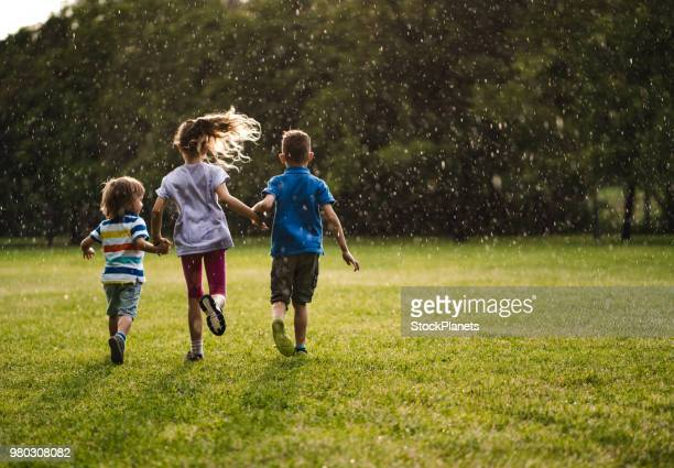 three kids holding hands and running from a rain