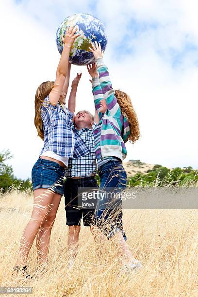 three kids holding up earth ball - guess jeans stock photos and pictures