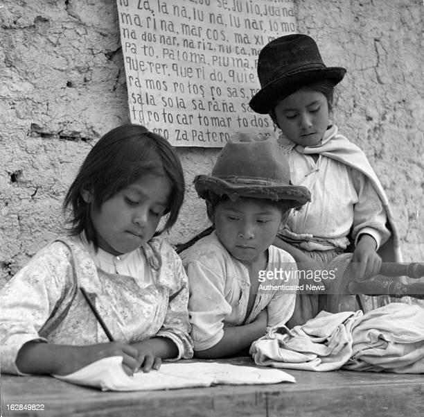 Three kids in Bolivia study outdoors while waiting for the construction of their school to be completed built by UNESCO an organization to help...