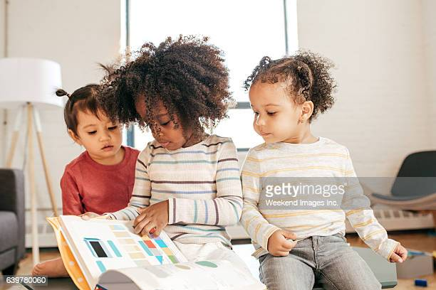 Three kids in daycare with book