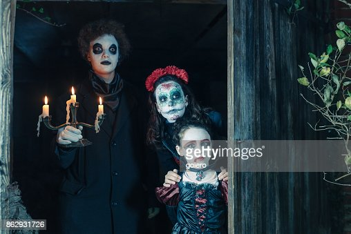 three kids in spooky halloween costumes behind door of barn stock photo getty images