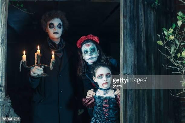 three kids in spooky halloween costumes behind door of barn