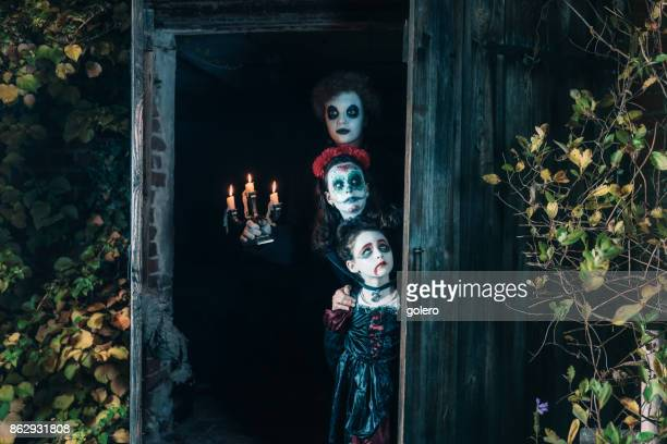 three kids in spooky halloween costumes hiding behind door of barn - zombie makeup stock photos and pictures