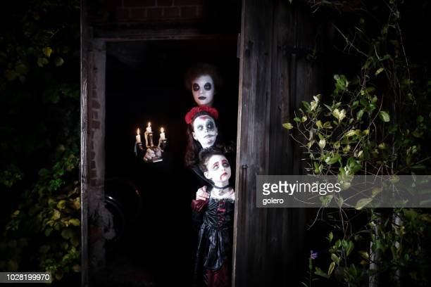 three kids in spooky halloween costumes in door of barn - ghost player foto e immagini stock