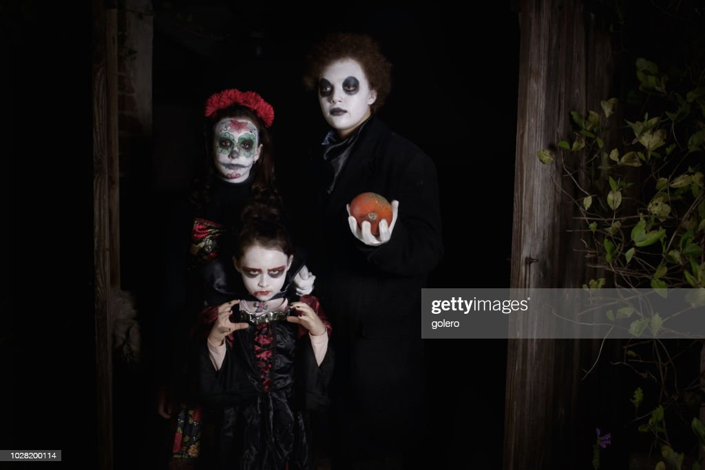 three kids in spooky halloween costumes in door of barn stock photo