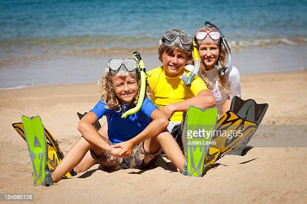 Three kids on sandy beach wearing snorkling gear