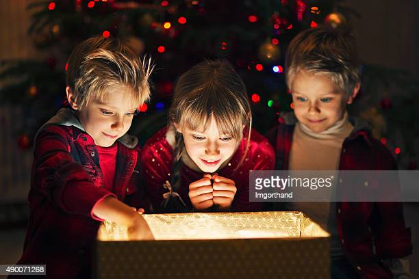 Three kids opening gift near the christmas tree