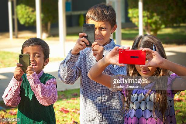 three kids photographing with their phones