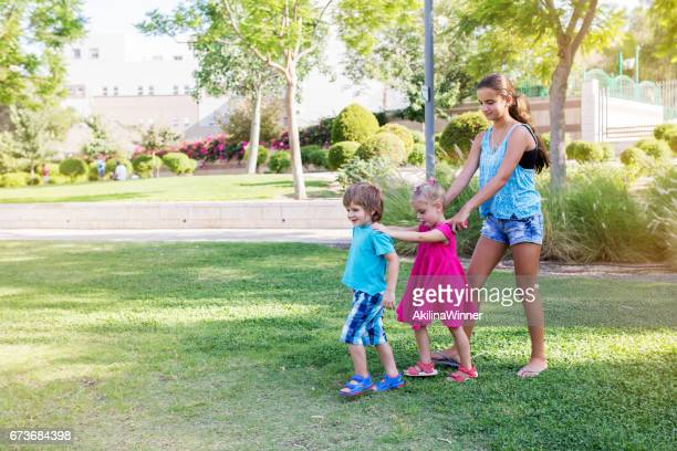Three kids playing at the park together.