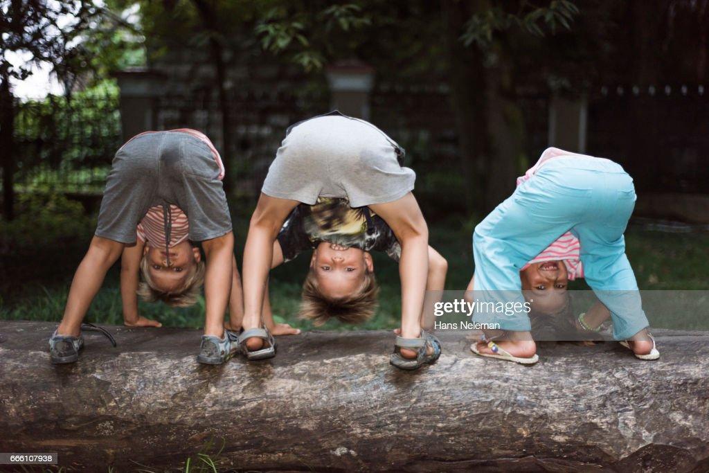 Three kids playing on fallen log : Stock Photo
