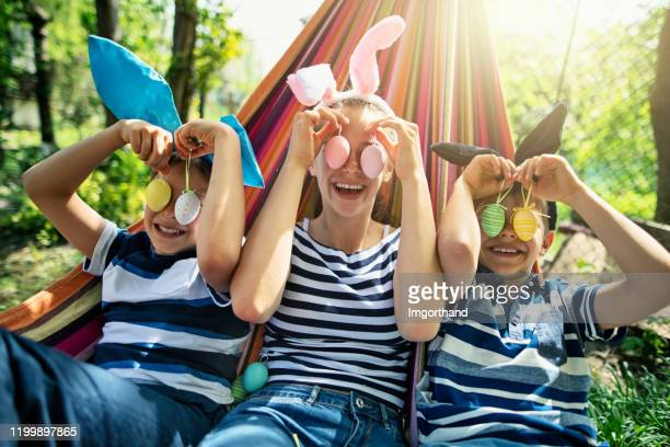 three kids playing with easter eggs found in the back yard - easter stock pictures, royalty-free photos & images