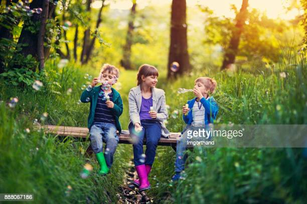 Three kids sitting on little bridge and blowing bubbles