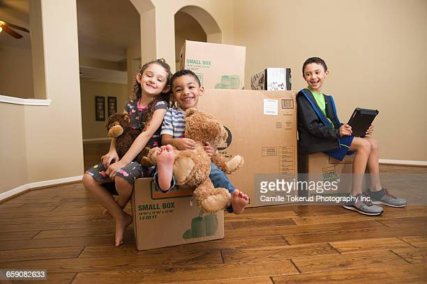Three kids sitting on moving boxes