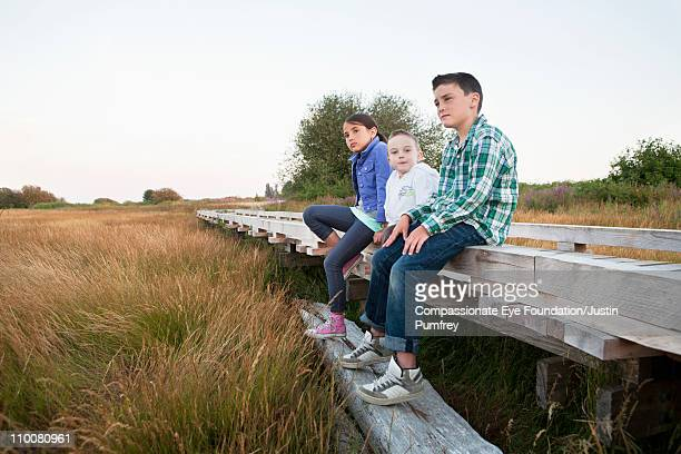 "three kids sitting on walkway in grassy field - ""compassionate eye"" - fotografias e filmes do acervo"