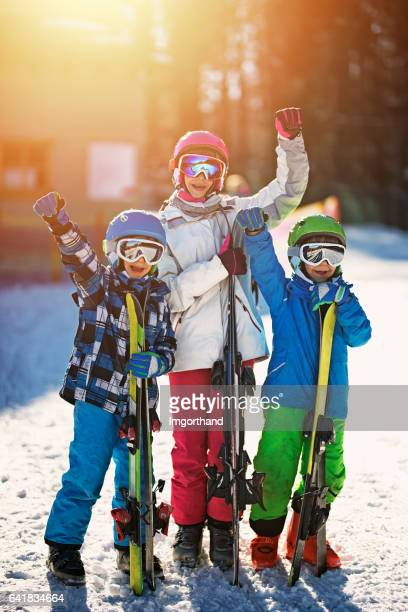 Three kids skiers with skis on sunny winter day