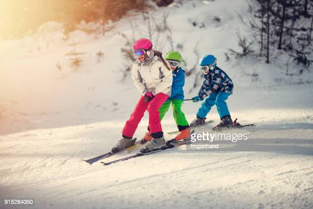 Three kids skiing in a beautiful winter forest.