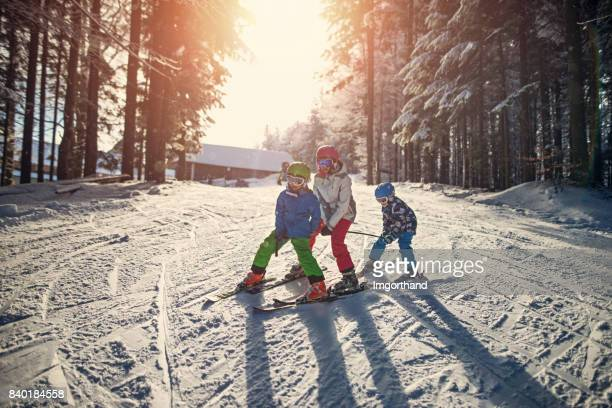 three kids skiing on a beautiful winter day - ski holiday stock photos and pictures